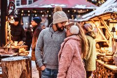 A happy couple in love, enjoying spending time together while embracing at the winter fair at a Christmas time royalty free stock image