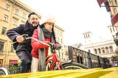 Happy couple in love enjoying winter time outdoor on vintage bicycle. Handsome hipster men with young women having fun together stock photography