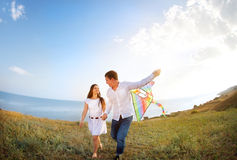 Happy couple in love with flying a kite on the beach. Happy young couple in love with flying a kite on the beach stock photography