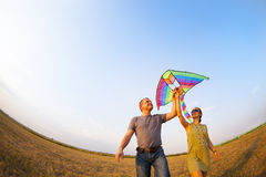 Happy couple in love with flying a kite. Happy young couple in love with flying a kite royalty free stock photo