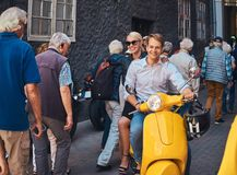 Happy couple in love - handsome stylish guy dressed in a white shirt and jeans and charming blonde girl wearing black. Dress riding on a yellow classic italian royalty free stock photo