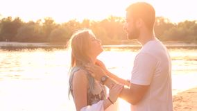 Couple in love on beach. Happy couple in love have a date. Hugging and kissing each other in beach near water / river during sunset in spring / summer stock video