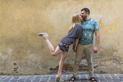 Happy  couple in love having fun against the wall of the house. Royalty Free Stock Photography