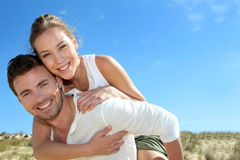 Happy couple in love having fun on the beach. Man giving piggyback ride to girlfriend on a sand dune Stock Photography