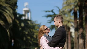 Happy couple in love having fun. Cute beautiful woman with a handsome man in a coat kissing. Against the backdrop of stock video