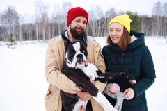 Happy couple in love having fun in the snow with his baby dog stock images