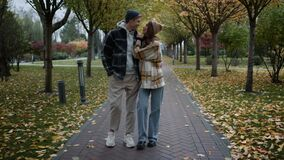Happy couple in love having romantic walk with joy and fun in foliage park.