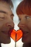 Happy couple in love hold heart shape lollipop Stock Photos