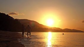 Happy couple in love holding hands running in tropical beach at sunset in slow motion. 1920x1080. Excited happy couple running in tropical beach at sunset in stock footage
