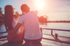 Happy couple in love hugging on the river dock at sunset. Young people chilling by the water royalty free stock images