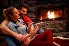 Happy couple in love hugging and using tablet together Stock Image