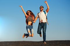 Happy couple in love jump on blue sky, wanderlust royalty free stock images