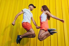Happy couple in love jumping against yellow wall. Young hipsters stock photos