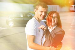 Happy couple in love, just bought new car from dealer and hold k royalty free stock images