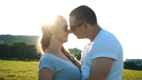Happy couple in love kissing in a field. Stunning sensual outdoor portrait of young stylish fashion attractive couple in love kissing in summer field stock video footage