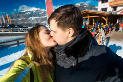 Happy couple in love kissing on winter ski resort at sunny day Royalty Free Stock Photography