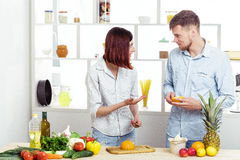 Happy couple in love in kitchen making healthy juice from fresh orange Stock Photography