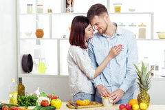 Happy couple in love in kitchen making healthy juice from fresh orange Royalty Free Stock Photography