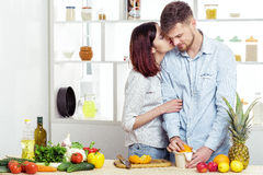 Happy couple in love in kitchen making healthy juice from fresh orange. couple is kissing royalty free stock photos