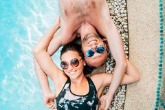Happy couple in love lying on the pool edge stock image