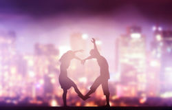 Happy couple in love making heart shape. City stock photo