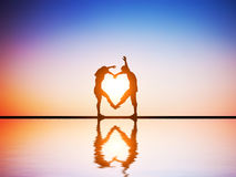 A happy couple in love making a heart shape. With their bodies at sunset with water reflection