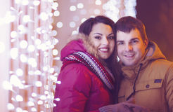 Happy couple in love outdoor in evening Christmas lights Royalty Free Stock Photos