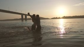 Happy couple in love playing in the river, hugging and kissing each other. The sunset makes this evening colorful stock video