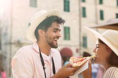 Couple in love sharing pizza on street Royalty Free Stock Image