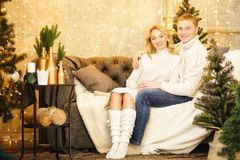 Happy couple of lovers in pullovers decorating Christmas tree. Christmas and new year at home. Young family together royalty free stock photos