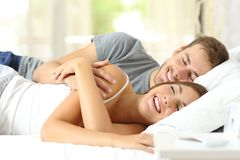 Happy couple in love sleeping together on bed stock photography