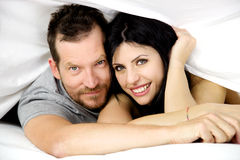 Happy couple in love smiling in bed Royalty Free Stock Photography
