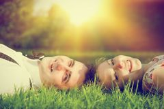 Happy couple in love smiling while lying on summer grass Royalty Free Stock Photo