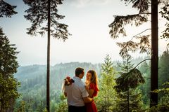 Happy couple in love is smiling and tenderly hugging in the forest at the background of the green mountains during the. Sunset Royalty Free Stock Images