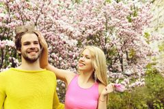 Happy couple in love in spring magnolia flowers. Couple in love. happy couple in love in spring magnolia flowers, smiling men and girl in garden with blossom royalty free stock images