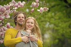 Happy couple in love in spring magnolia flowers. Smiling men and girl in garden with blossom tree outdoor on natural background stock image