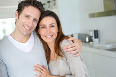 Happy couple in love standing in kitchen Stock Photos