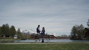 Happy couple in love standing together with hands raised on lakeside wooden bench with beautiful mountain view. Rear. View. General plan 4k stock footage