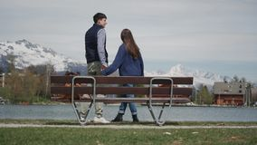 Happy couple in love standing together with hands raised on lakeside wooden bench with beautiful mountain view. Rear. View 4k stock video