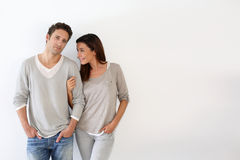 Happy couple in love standing on white wall Royalty Free Stock Photo