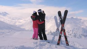 Couple in Love Stands on the Top of the Snowy Mountain and Moves their Hands. A happy couple in love stands on the top, hugs, kisses and moves their hands stock video footage