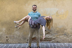 Happy  couple in love on the street in front of a stone wall. Royalty Free Stock Photo