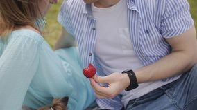 A loving couple on a date by the river. A guy is feeding a girl with strawberries. Happy couple in love stroll along the river bank. Dating outdoors stock video footage