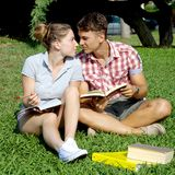 Happy couple in love studying with books in park Stock Photo