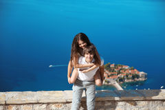 Happy couple in love summer vacations. Young man piggybacking his beautiful girlfriend over sea, while laughing at camera. Sveti S Stock Photo