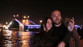 Happy couple in love taking selfie. A movable Palace Bridge St. Petersburg at the background. City illumination at night. Happy couple in love smiling, taking stock video