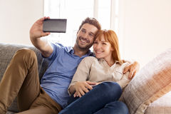 Happy couple in love taking a selfportrait with a cell phone. Stock Photography