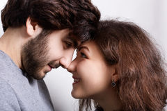 Happy couple in love touching noses smiling and looking at each other`s words. Close-up nose to nose. Couple in love touching nose. S. Young couple standing Royalty Free Stock Photography