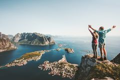 Happy Couple love and travel raised hands on cliff. In Norway man and woman family travelers lifestyle concept summer vacations outdoor Lofoten islands royalty free stock photos