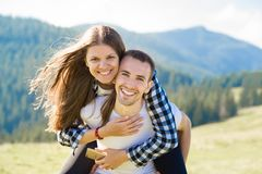 Happy couple in love walk on top of mountains. Young happy man holds his girlfriend royalty free stock photography